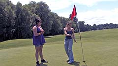 Beth and Georgia miming on a golf course