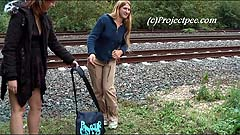 Kathy and Lindsay peeing by a railway track